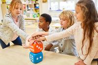 Gruppe Kinder stapelt Hände als Team Konzept