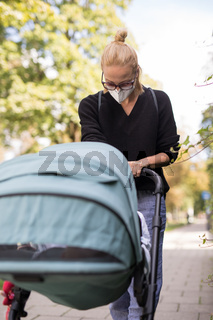 Worried young mom walking on empty street with stroller wearing medical masks to protect her from corona virus. Social distancing life during corona virus pandemic
