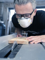 Man with a dust mask and goggles working on a circular saw