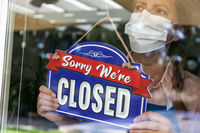 Female Store Owner Wearing Medical Face Mask Turning Sign to Closed in Window