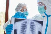 Ärzte in Klinik mit Röntgenbild einer Lungenentzündung