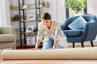 young woman unfolding carpet at home