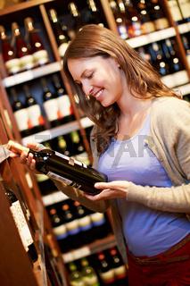Frau kauft Wein im Supermarkt