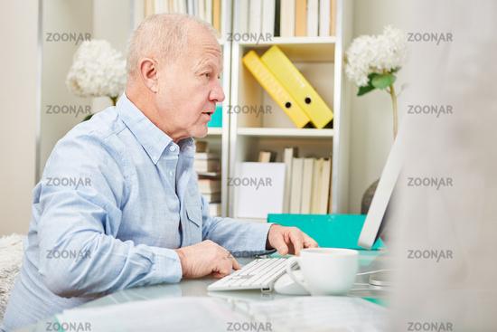 Senior vor Computer schaut auf Monitor