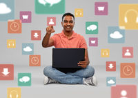 happy indian man with laptop over app icons