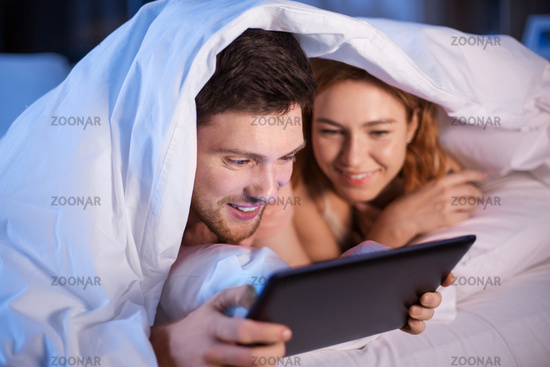 happy couple using tablet pc in bed at night