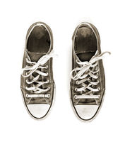 Old black sneakers isolated on white background