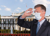 Senior man wearing face mask taking his temperature to check for fever