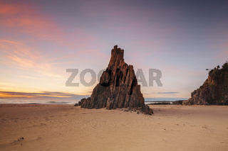 Pyramid sea stack on beach with beautiful sunrise sky with red clouds