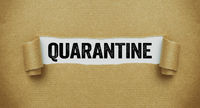 Torn paper revealing the word Quarantine