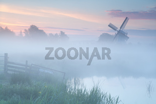 misty sunrise over Dutch windmill on farmland
