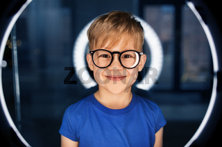 boy in glasses over illumination in dark room