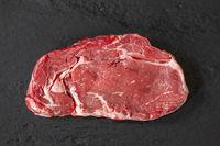 Überblick über ein rohes Steak auf schwarzer Scheibe