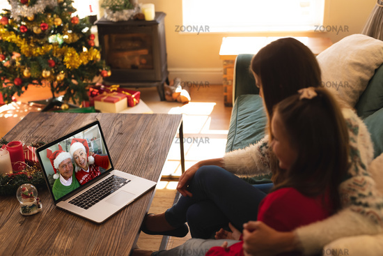 Woman and daughter sitting on the couch having a videocall with senior couple in santa hats on lapto
