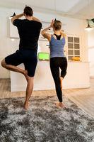 White caucasian couple do tree pose yoga at home