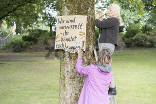 XR Extinction Rebellion Bielefeld campaigning with handmade posters for the protection of trees