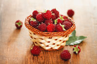 Small basket with ripe raspberry on wooden table