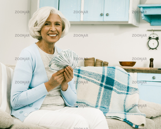 White haired senior woman hold money or payment
