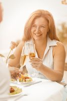 Happy woman holds glass of white wine smiling while looking to her husband. Mature caucasian couple celebrates wedding anniversary while sitting in cafe outdoors near sea. Toned image