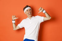 Concept of sport, fitness and lifestyle. Image of confident middle-aged man pointing at himself, bragging about achievement, wearing clothes for workout, standing over orange background