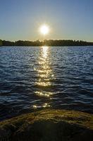 Die Sonne geht über einem See in Schweden unter