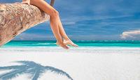 Woman on palm on Caribbean beach