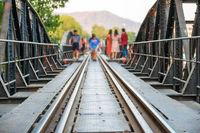 People walking by rail track of railroad bridge