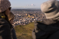 A group of friends on top of Arthurs Seat hill over looking the city of Edinburgh and Edinburgh Castle