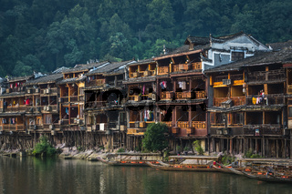 Old wooden stilt houses and boats in Fenghuang