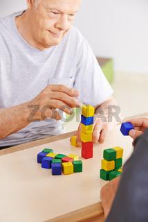 Mann mit Demenz spielt mit Bausteinen