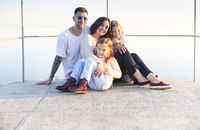 Young happy family on concrete ground in sunlight