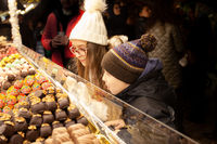 Happy children choosing sweets in christmas market