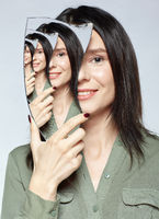 Smiling female with mirror shard in hand and multiple reflections..