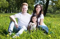 Family with pet dog in park