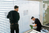two male professional cleaners cleaning blinds on a large window front with micro fiber cloths