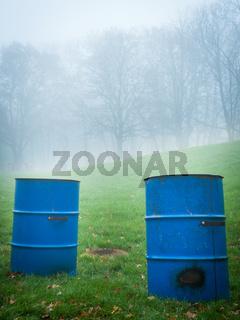 Blue trash bins in a foggy park