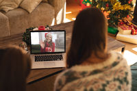 Rear view of woman and son having a videocall with woman in santa hat waving while holding gift box