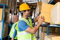 Indian warehouse worker put cardboard box in shelf