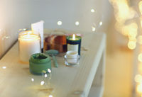 Burning candles and containers with various skincare cosmetics