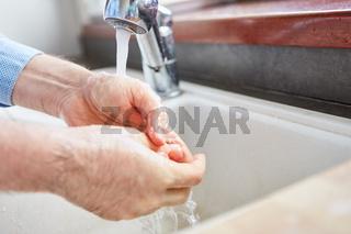 Senior beim Händewaschen mit Wasser und Seife