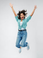 happy young woman jumping over grey background