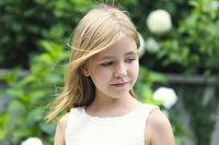 Happy little girl in green summer garden