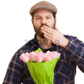 Bearded young handsome man holding a bouquet of pink tulips
