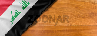 National flag of Iraq on a wooden background with copy space