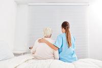 Pflegekraft hilft Seniorin im Pflegeheim vom Bett