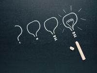 Hand drawn light bulb on a blackboard, a question becomes an idea