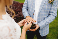 Bride puts wedding ring on groom finger. Boutonniere. Blurred background