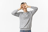 Portrait of funny middle-aged guy making faces, showing hand glasses around eyes as if looking through binoculars, standing over white background