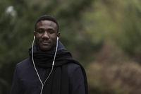 Portrait of Young Black Man Listening to Earphones in Park