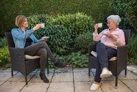 Seniorin und Pflegekraft trinken Kaffe mit Sicherheitsabstand im Garten
